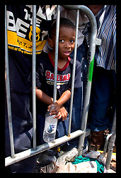 2nd Sept, 2005. A young boy is trapped against railings in the baking sun awaiting evacuation from the hellish Superdome in New Orleans.