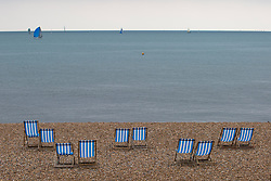 © Licensed to London News Pictures. 07/05/2017. Brighton, UK. Deckchairs stand unused on the beach in Brighton and Hove as low temperatures and grey clouds are hitting the seaside resort. Photo credit: Hugo Michiels/LNP