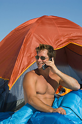 good looking man on a cell phone outside a tent