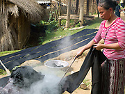 Meuay, a Iu Mien (Yao) ethnic minority woman boiling indigo dyed cotton fabric in Mak Bao (a trailing forest fruit) to fix the colour, Ban Hom Phan, Houaphan province, Lao PDR. Meuay buys the cotton fabric from a nearby Tai Deng village and after dyeing the fabric many times to build up the colour she sells to local Iu Mien women to make their traditional clothing. One of the most ethnically diverse countries in Southeast Asia, Laos has 49 officially recognised ethnic groups although there are many more self-identified and sub groups. These groups are distinguished by their own customs, beliefs and rituals.