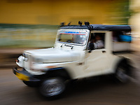 JAIPUR, INDIA - CIRCA NOVEMBER 2018: Jeep in the streets of Jaipur with tourists. Jaipur is the capital and the largest city of the Indian state of Rajasthan. Jaipur is also known as the Pink City, due to the dominant color scheme of its buildings and a popular tourist destination.