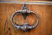 An old iron door knocker on the door of a resident of Saignon, France