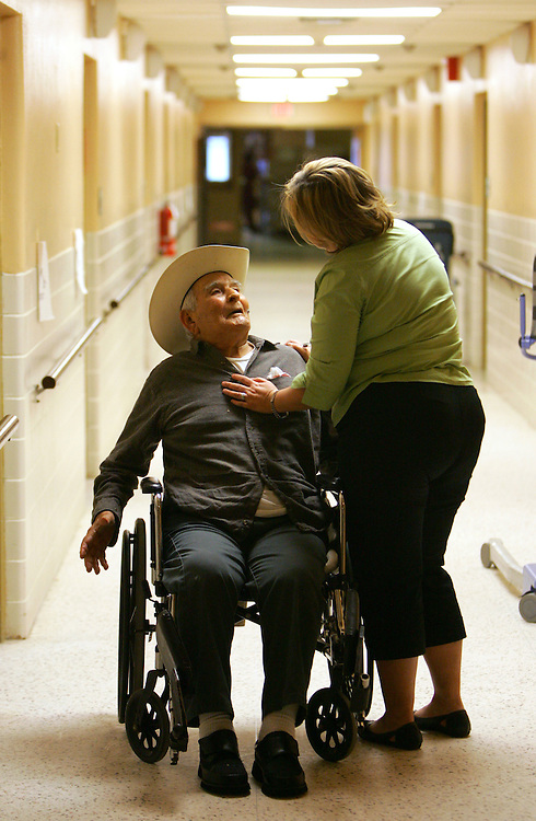 San Juan, TX - 30 Dec 2008 - .San Juan Nursing Home employee Norma Hinojosa greets longtime resident Panfilo Vela on his way to dinner on Tuesday evening.  The Nursing Home, which is affiliated with the Diocese of Brownsville, is one of the highest rated in Hidalgo County..Photo by Alex Jones / ajones@themonitor.com