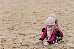 A young girl plays in the sand on a cold, windy  day at Fistral Beach in Newquay, Cornwall.