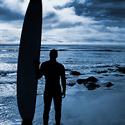 A surfer preparing for an afternoon of surfing on the Californian coast. (Santa Cruz, US)<br /> <br /> + ART PRINTS +<br /> To order prints or cards of this image, visit:<br /> http://greg-stechishin.artistwebsites.com/featured/blue-coast-surf-greg-stechishin.html