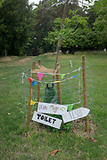 While park conveniences are still closed, makeshift signs pointing to where nearby toilets are located during the Coronavirus pandemic lockdown are, are attached to the protective fence around a yourg tree in Ruskin Park, Lambeth, on 30th June 2020, in London, England.