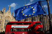 The stars of the EU flag fly over a London bus and the Houses of Parliament in Westminster, seat of government and power of the United Kingdom during Brexit negotiations with Brussels, on 23rd November 2017, in London England.