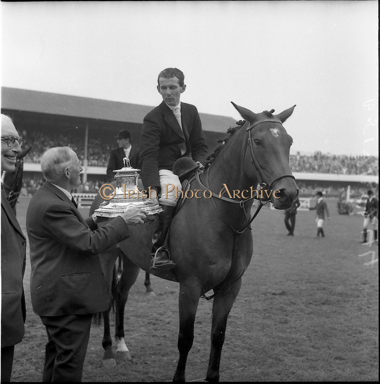 """06/08/1960<br /> 08/06/1960<br /> 06 August 1960<br /> R.D.S Horse Show Dublin (Saturday). """"Dundrum"""", owned by Mr James Wade, Camas, Cashel, Co. Tipperary and ridden by Mr. Thomas Wade (brother of James) won the Wylie Perpetual Challenge Trophy, the 'Civillian' Championship of the Show, at the Dublin Horse Show. Picture shows the Hon. W.E. Wylie, Q.C., the diner of the trophy, presenting the prize to Mr. Thomas Wade."""