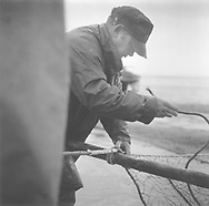 Salmon netter Mike Smith working to repair one of his 'jumper' nets at St. Cyrus, Aberdeenshire.<br /> Ref. Catching the Tide 08/01/09 (26th June 2001)<br /> <br /> The once-thriving Scottish salmon netting industry fell into decline in the 1970s and 1980s when the numbers of fish caught reduced due to environmental and economic reasons. In 2016, a three-year ban was imposed by the Scottish Government on the advice of scientists to try to boost dwindling stocks which anglers and conservationists blamed on netsmen.