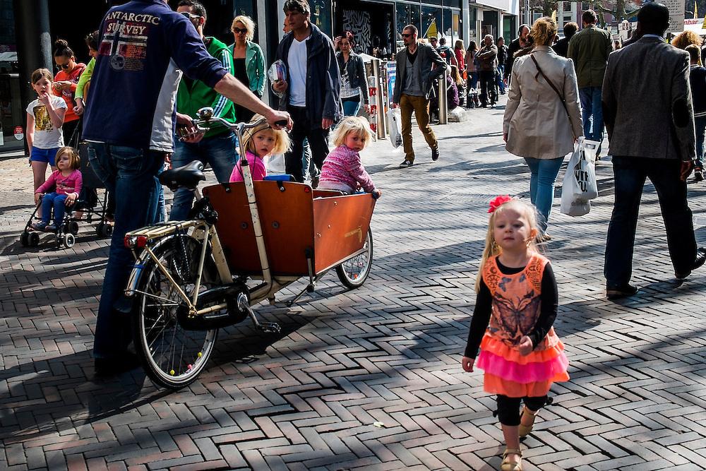 Nederland, Utrecht, 29 mrt 2014<br /> Meisje in kleurige kleding loopt over straat en wordt nageken door andere kleine kinderen die ook kleurig gekleed zijn maar in een bakfiets zitten. <br /> Foto (c) Michiel Wijnbergh