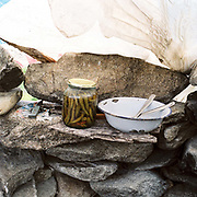 A jar of pickled chillies and an enamel bowl and spoons on a wall of a basic stone built sheepfold at the Urdele Pass in a remote area of the Carpathian Mountains, Romania