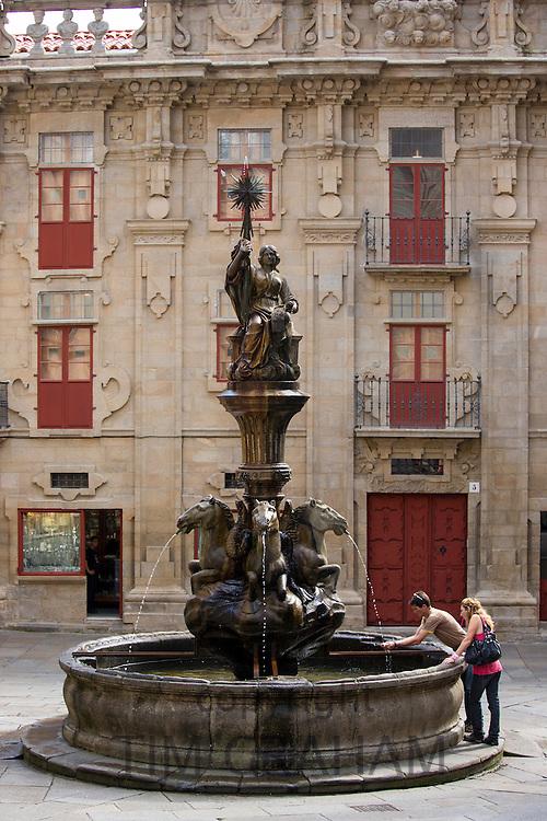 Young couple at Dos Cavalos fountain of horses, Praza das Praterias, in Santiago de Compostela, Galicia, Spain