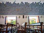 30 MARCH 2013 - BANGKOK, THAILAND: A man prays under a large fresco in the sanctuary of Holy Redeemer Catholic Church in Bangkok, Thailand. Holy Redeemer is one of the largest Catholic churches in Thailand.       PHOTO BY JACK KURTZ