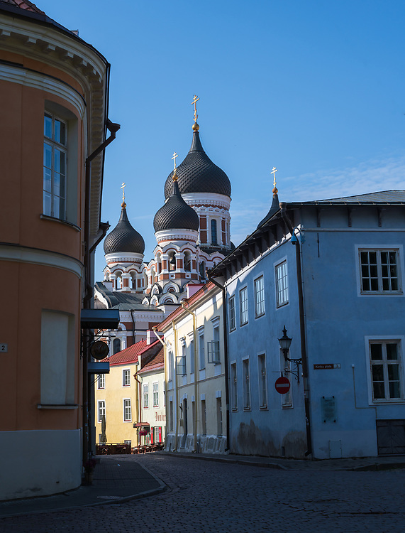 Tallin, Estonia -- July 23, 2019. A vertical shot of a side street in Tallin, Estonia; domes of Alexander Necsky Cathedral are in the background