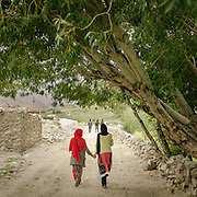 Two girls walking hand in hand in Zood Khun village. Chapursan valley on the border with Afghanistan.