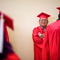Calvin Tsosie chats with his classmates as they line up for the New Life Learning Center graduation ceremony Friday at Lighthouse Church in Gallup.
