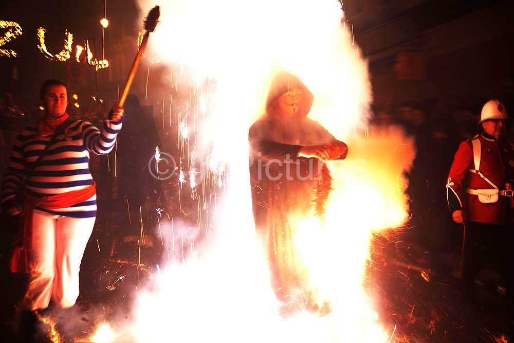 Lewes, UK. Monday 5th November 2012. Member of Lewes Borough bonfire society lights a string of fire crackers. Bonfire Night celebration in the town of Lewes, East Sussex, UK which form the largest and most famous Guy Fawkes Night festivities. Held on 5 November, the event not only marks the date of the uncovering of the Gunpowder Treason and Plot in 1605, but also commemorates the memory of the 17 Protestant martyrs from the town burnt at the stake for their faith during the Marian Persecutions of 1555–57. There are six bonfire societies putting on parades involving some 3,000 people.