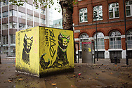 A yellow cube in a London street with graffiti during autumn