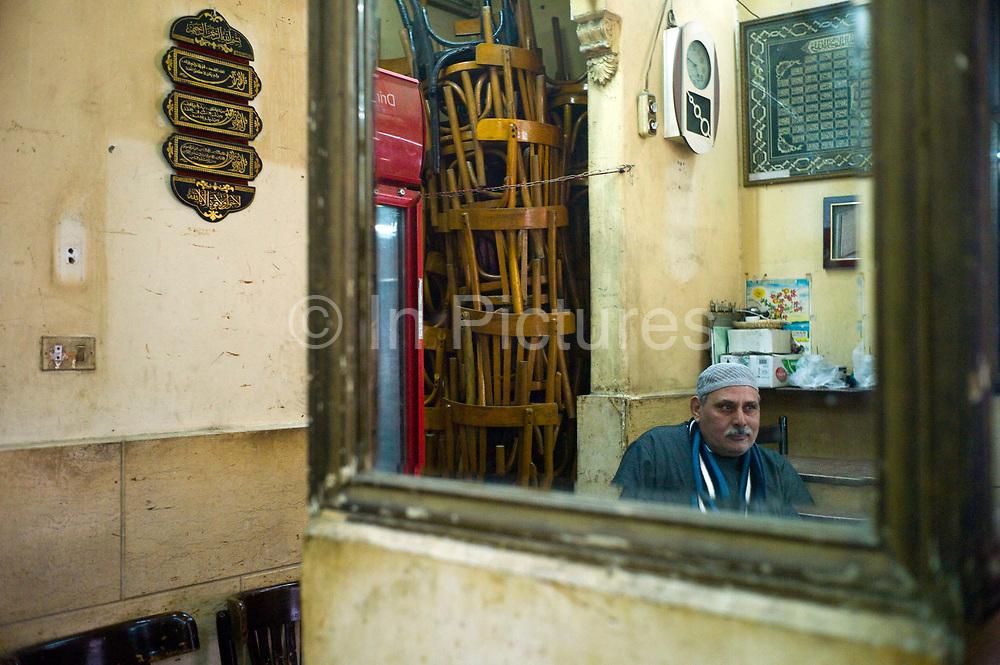 A man sits inside the El Nadawa El Thaqafiya cafe, Cairo, Egypt