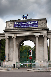 London, August 12th 2014. Two protesters from Fathers For Justice wave at the passing traffic from atop Decimus Burton's Ionic screen entrance to Hyde Park adjacent to Apsley House at  Hyde Park Corner.