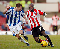 Photo: Leigh Quinnell.<br /> Brentford v Huddersfield Town. Coca Cola League 1. 21/01/2006. Brentfords Lloyd Owusu finds a way past Huddersfields David Mirfin.