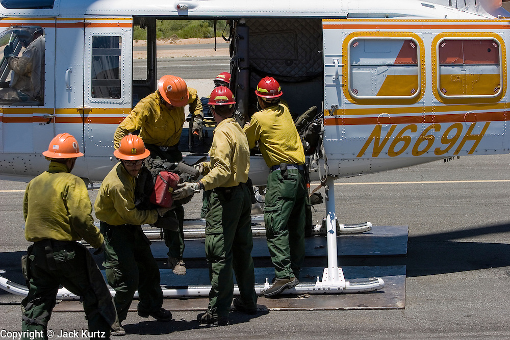 26 JUNE 2005 - CAVE CREEK, AZ:  Members of the Horseshoe Meadows Hotshots get off a Bell Super 205 helicopter at the Skyranch at Carefree, a private airport in Carefree, after returning from the Cave Creek Complex fire line Sunday afternoon. The airport has been allowing the team fighting the Cave Creek Complex fires to use their facilities as the helibase for the fire. The Cave Creek Complex fire was the third largest wildfire in the state of Arizona to date, after the Rodeo-Chediski fire and Wallow Fire. The fire started on June 21, 2005 by a lightning strike during a monsoon storm and burned 243,950 acres (987.2 km2).   PHOTO BY JACK KURTZ