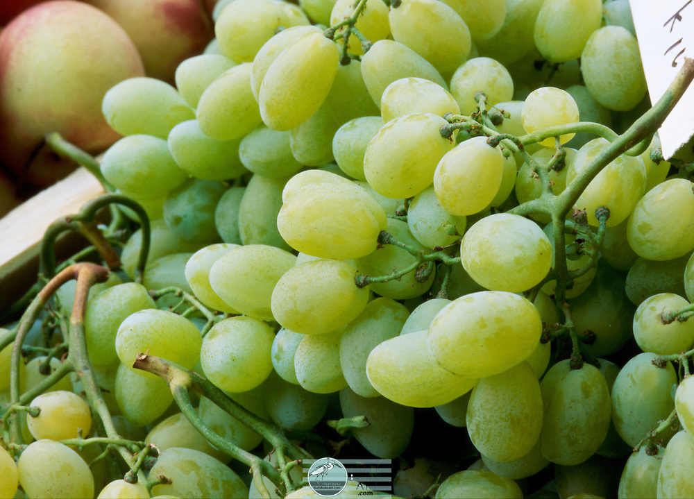 Green grape stalks displayed at a fresh produce market in Naples, Italy.