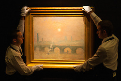 Sotheby's, London, December 5th 2014. World renowned aution house Sotheby's is to offer a collection of British and Continental masters to be sold at auction on December 10th 2014. PICTURED: Sotheby's gallery technicians hang Belgian artist Emile Claus's impressionist painting of Waterloo Bridge with the Houses of Parliament and Big Ben in the background, which is expected to fetch between £200-300,000 at auction.