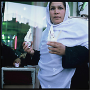 An Afghan woman buys soft ice cream at a bazaar in downtown Kabul.