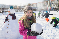 Portrait of girl holding snowball on field
