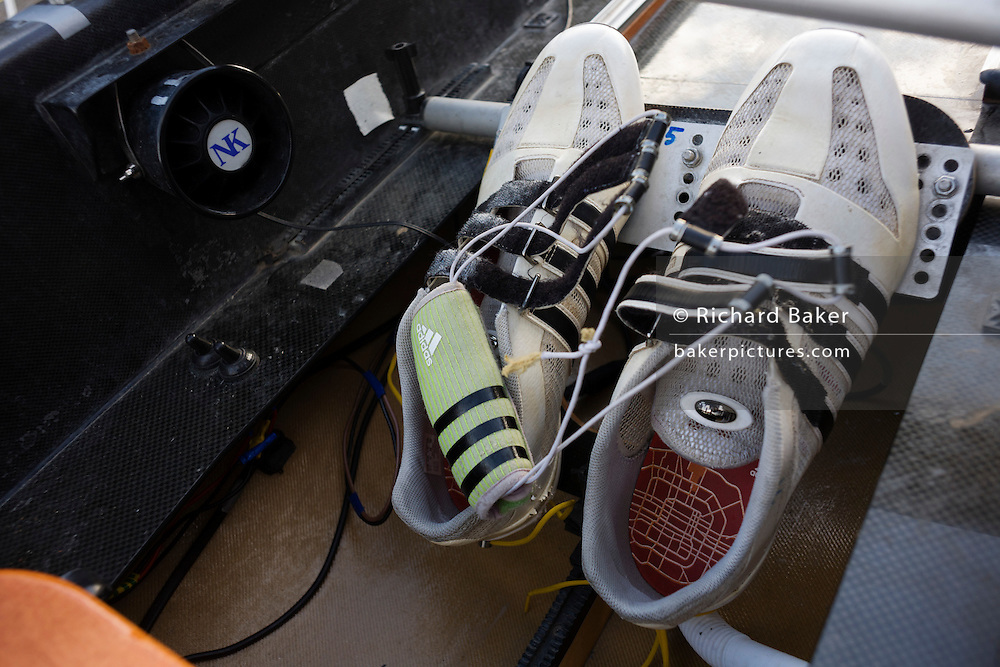 A pair of trainers attached to the foot plate on boat belonging to the Oxford University rowing team outside a boathouse in Putney, West London before a winter training session. First raced in 1829 the boat race between Oxford and Cambridge unbiversities is one of the oldest sporting events in the world. It is nowadays watched by thousands along the banks of The Thames Tideway, between Putney and Mortlake in London and by millions more on TV around the world. The footplate is a piece of the boat to which the rower's feet are attached, either by tying their actual shoes in, or (more often) by putting their feet into a permanently-attached pair of shoes. (also Foot stretcher and footchock).