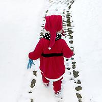 Amsterdam, 19 december 2009..Peuter in rood kerstman- kabouterpakje ontdekt voor het eerst van haar leven sneeuw..Toddler in red Father Christmas suit meets snow for the first time in her life.