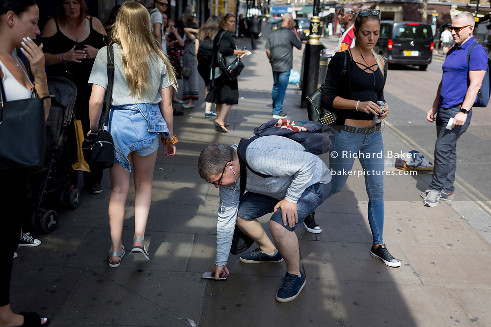Before others step on it, a man stoops to pick-up his dropped iPhone in the street, on 29th August 2019, in Charing Cross Road, London, England.