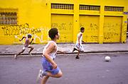 Boys playing football on a Sao Paulo city street, Brazil.