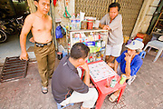09 MARCH 2006 - HO CHI MINH CITY, VIETNAM: Men play a board game similar to checkers on a street in Ho Chi Minh City (formerly Saigon), Vietnam. Photo by Jack Kurtz