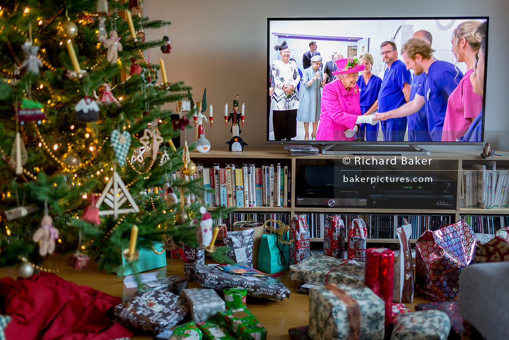 Christmas presents remain unopened beneath a Christmas tree as Queen Elizabeth meets NHS staff during her speech to the nation on Christmas Day, a tradition started in 1932 and which she first broadcast on television in 1957, on 25th December 2019, in Bristol, England.