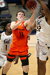 Feb 25, 2021; Berkeley, California, USA; Oregon State Beavers guard Zach Reichle (11) goes in for a reverse layup against California Golden Bears defenders Joel Brown (1) and Andre Kelly (22) during the second half of an NCAA college basketball game at Haas Pavilion. Mandatory Credit: D. Ross Cameron-USA TODAY Sports