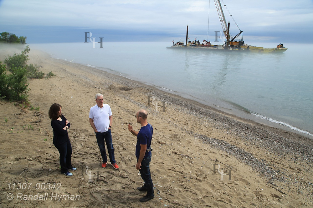GLPF's Amy Elledge, Communications Manager, and Steve Cole, VP of Programs, talk with Healthy Ports PI Brian Davis as Army Corps of Engineers use crane and barge to construct underwater rubble ridge designed to disrupt wave energy and reduce shoreline erosion and habitat loss at Illinois Beach State Park; Zion, Illinois.