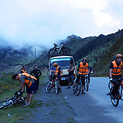 """Mountain Biking on Death Road, Bolivia...A tour group of Mountain Bikers stop to rest and be briefed about the next stage of the journey by their tour leader, biking down infamous narrow dirt road, most of the road no wider than 3.2meter's, is cut into the side of the mountain with sheer drops to the left of up to 600 meter's with virtually no safety rails on the winding steep decent....The North Yugas Road is a 64 Kilometer road leading from La Paz to Corioico. It is legendary for it's extreme danger and in 1995 the Inter American Development Bank christened is as the """"world's most dangerous road"""".. The road was built in the 1930's during the Chaco War by Paraguayan prisoners to connect the Amazon rainforest region of Northern Bolivia to it's capital City La Paz. One estimate is that 200 to 300 travelers were killed yearly along the road. On 24 July 1983, a bus veered off the Yungas Road and into a canyon, killing more than 100 passengers in what is said to be Bolivia's worst road accident..A new stretch of the La Paz-Coroico highroad was opened in 2006 to bypass the notorious stretch known as death road..The danger of the road has now made it a popular tourist destination starting in the 1990's and drawing thrill-seekers and mountain bike enthusiasts who ride on the 64km mainly downhill stretch from La Cumbre, a 4,700 meter peak to Yolosa, a decent of 3600 meter's (11,800 feet). The journey includes breathtaking views of snow covered peaks and towering cliffs and starts along modern asphalted road before entering the jungle itself and the most dangerous and notorious part of the ride. The infamous narrow dirt road, most of the road no wider than 3.2meter's, is cut into the side of the mountain with sheer drops to the left of up to 600 meter's with virtually no safety rails on the winding steep decent..There are now many tour operators catering to this activity, providing information, guides, transport and equipment. Nevertheless, the Yungas Road remains dangerou"""