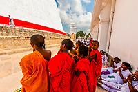 Novice Buddhist monks stand with praying pilgrims, Ruwanwelisaya Dagoba (Stupa) in the ancient city of Anuradhapura, Sri Lanka. Also known as the Ruwanweli Maha Seya, or Great Stupa is a sacred place of pilgrimage and worship in the ancient city of Anuradhapura.
