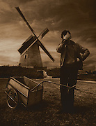 A man with a cart covers his face while posing in from of a large windmill in Achicourt, France