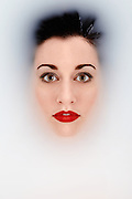 Portrait of a young woman with her head partially submerged in a bath. She appears to be bathing in 'milk.' Image taken by Bristol based portrait photographer Jonathan Bowcott