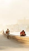 Tourists and street guitarist near sea bay, Havana, Cuba