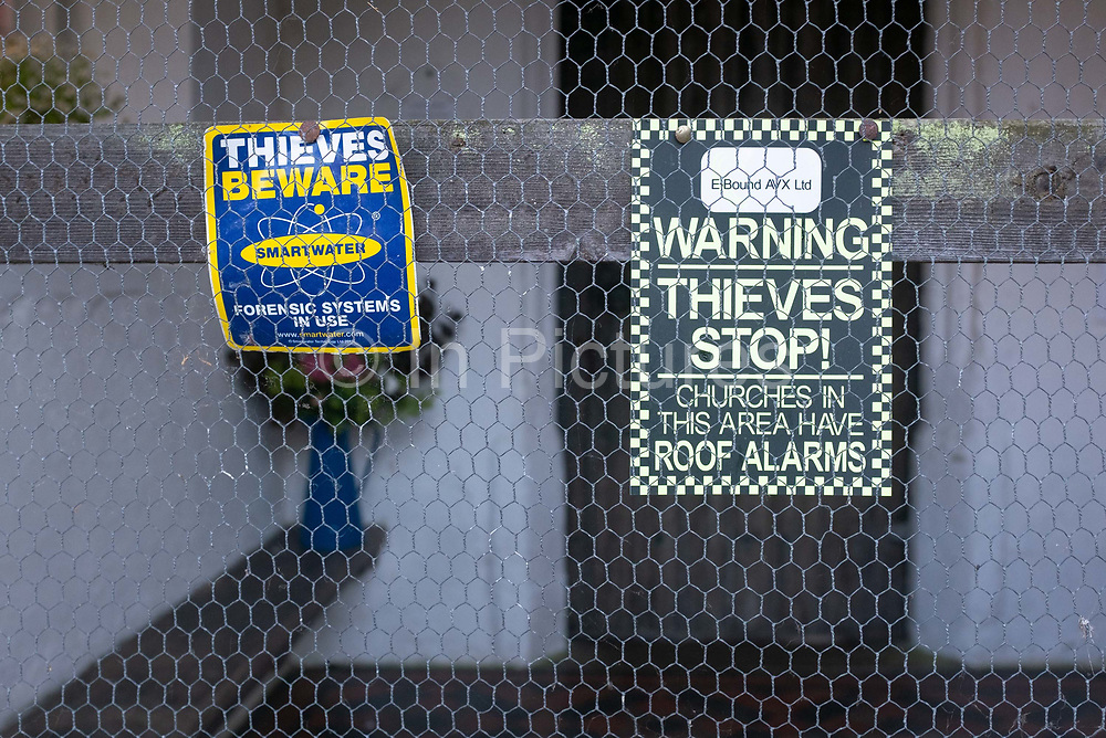Anti-theft signs attached to chicken wire mesh at the front door of All Saints Church in Hartest, on 10th July 2020, in Hartest, Suffolk, England.