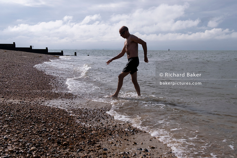 A cold and tired wild swimmer hobbles over beach shingle after a swim in the cold tidal waters of the Thames Estuary, on 25th July 2021, in Whitstable, England.