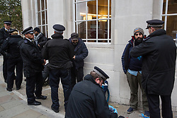 London, UK. 11 October, 2019. Police officers carry out stop and searches on three men of colour from charity Who Is Hussain? attending an Extinction Rebellion protest outside the main entrance to the BBC's New Broadcasting House on the fifth day of International Rebellion protests.