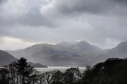 © Licensed to London News Pictures. 11/12/2015. Glenridding UK. Picture shows snow forming on the mountains above Glenridding next to Ullswater lake. The clean up operation in the Village of Glenridding continues today despite heavy overnight rain & hail stones this morning. Photo credit: Andrew McCaren/LNP