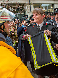 © Licensed to London News Pictures. 23/12/2019. London, UK. London Fire Brigade Commissioner Dany Cotton holds a gift bag presented by firefighters from overseas as a Guard of Honour is held in London. Firefighters from across the UK and several from overseas attended the unofficial event outside the brigades headquarters in Union Street. Commissioner Cotton is retiring in the wake of the Grenfell Fire. Photo credit: Peter Manning/LNP