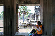 A woman tourist covers her arms with additional sleeves to adhere to the Theravada Buddhist dress code whilst sitting on a stone window ledge in Angkor Wat Siem Reap, Cambodia.  Angkor Wat is Cambodia's main tourist destination and one of UNESCO's world heritage sites.