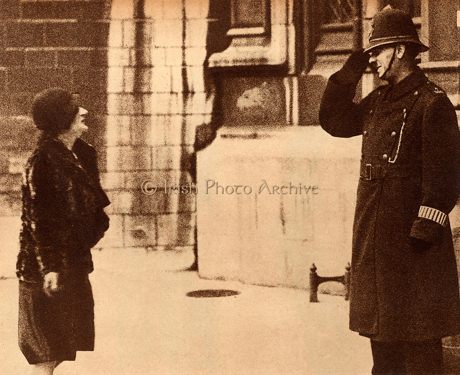 Ellen Cicely Wilkinson (1891-1947) British Labour (Socialist) politician and feminist, Member of Parliament for Middlesborough 1924-1931, being saluted by a duty police officer as she enters the Houses of Parliament, 1928.
